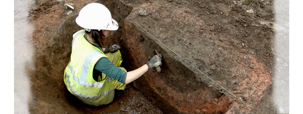 A GGAT Archaeologist excavating a half sectioned pit feature